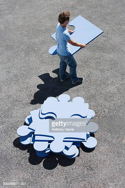 Young man holding large blue jigsaw piece, elevated view