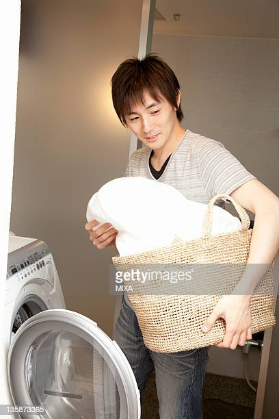 Young man holding laundry basket