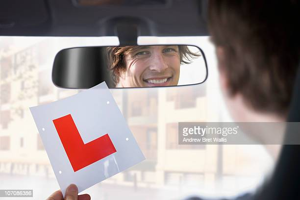 Young man holding learner driver L plate in car