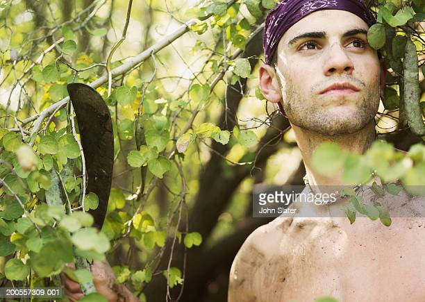 young man holding machete amongst foliage - machete stock pictures, royalty-free photos & images