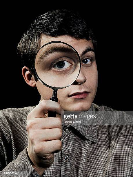 Young man holding magnifying glass over eye, portrait