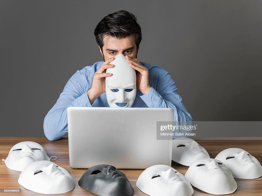 Young man holding mask in front of computer : Stock Photo