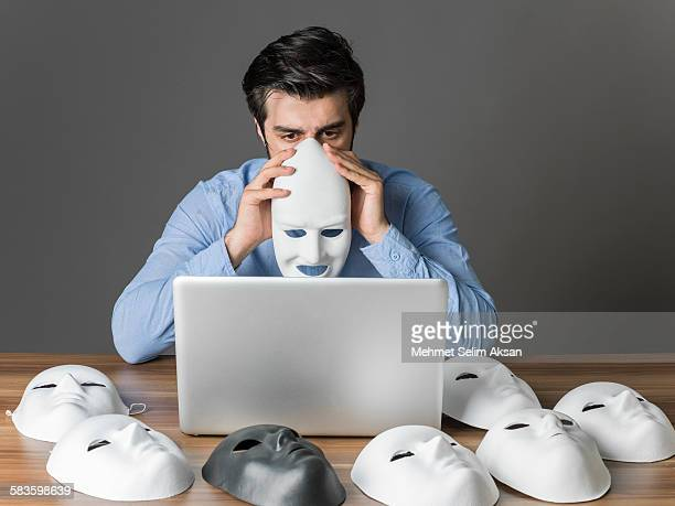 Young man holding mask in front of computer