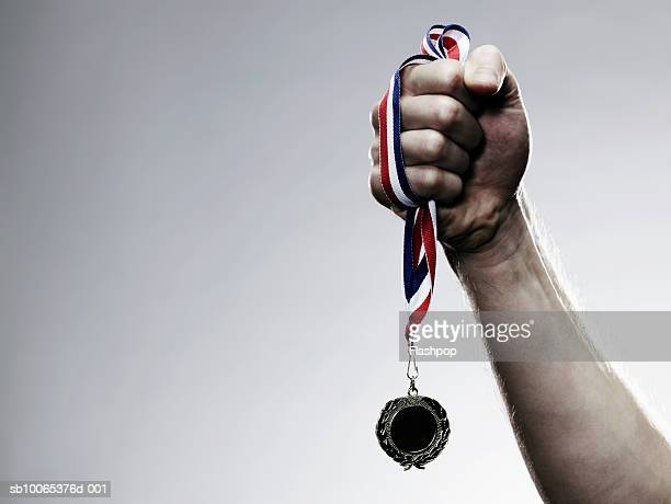 young man holding medal, close-up - medalist stock pictures, royalty-free photos & images