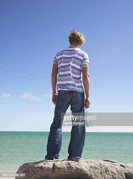 Young man holding message in a bottle looking out to sea, rear view