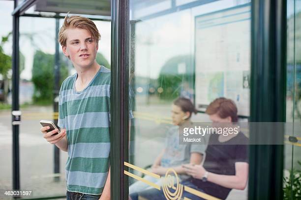 Young man holding mobile phone while waiting with friends at bus stop