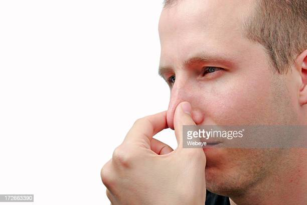 Young man holding nose to signify a bad smell