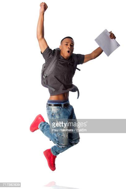 Young Man Holding Notepad While Jumping Against White Background