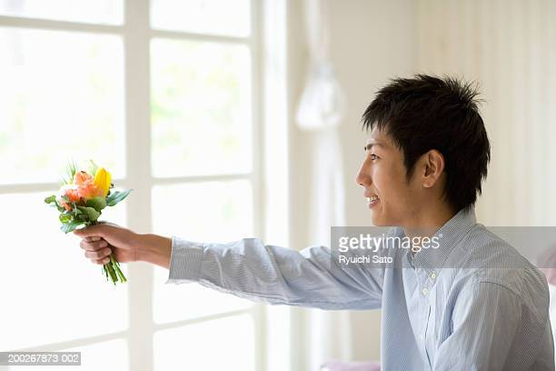 Young man holding out bunch of flowers, smiling, profile