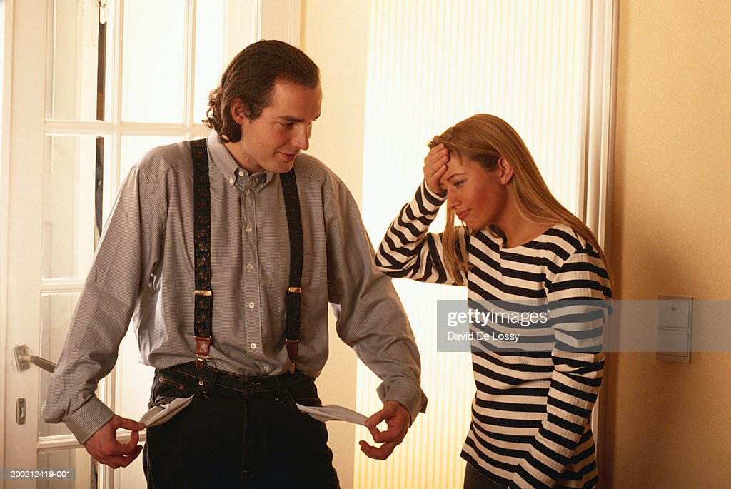 Young man holding out empty pockets, in front of woman : Stock Photo