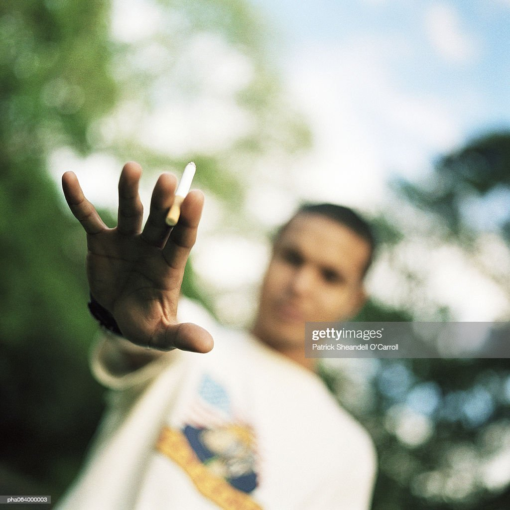 Young man holding out hand with cigarette, blurred background. : ストックフォト