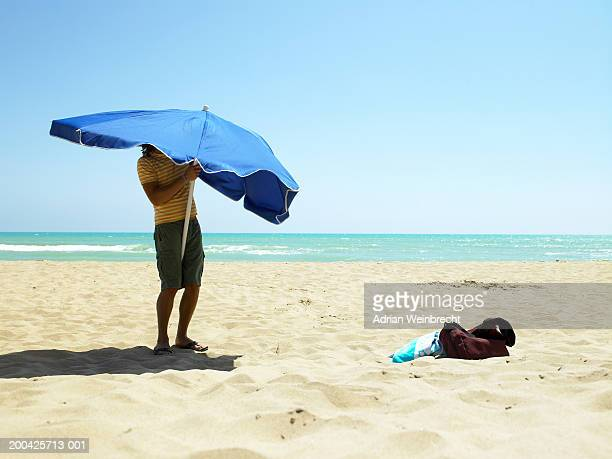 young man holding parasol on beach, low section - bemühung stock-fotos und bilder