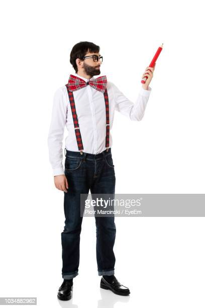 young man holding pencil while standing against white background - suspenders stock pictures, royalty-free photos & images
