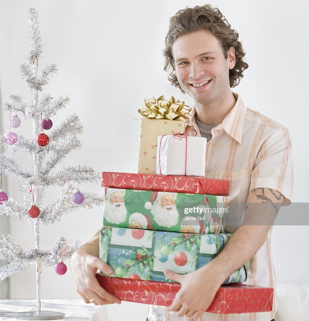 young man holding pile of christmas presents smiling portrait stock photo