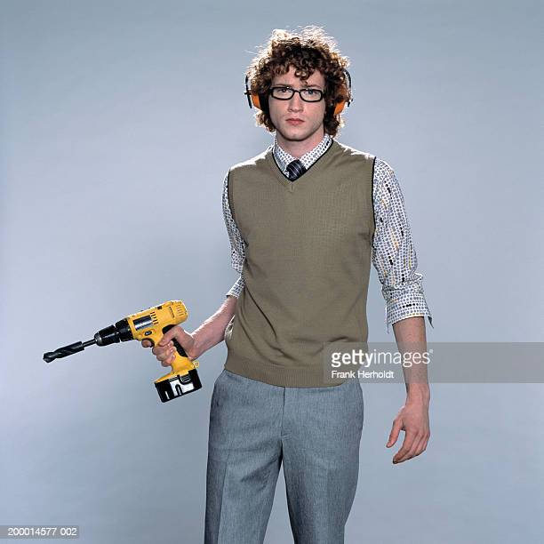 Young man holding power drill, portrait