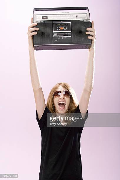 Young man holding radio above head screaming