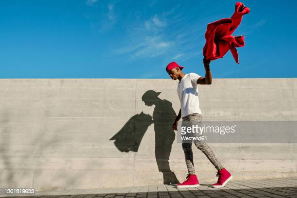 young man holding red jacket and walking against concrete wall - surrounding wall stock pictures, royalty-free photos & images