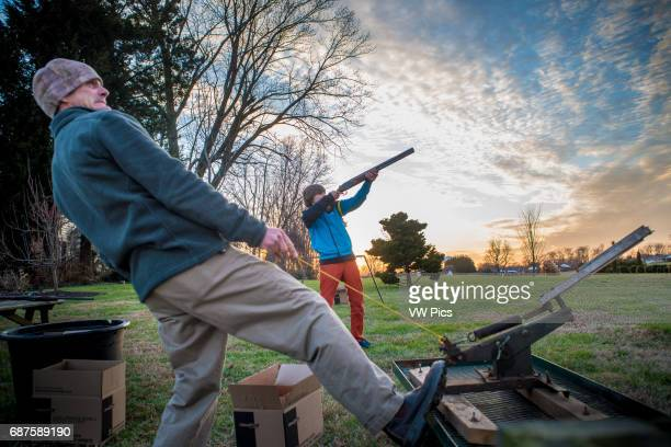 Young man holding rifle aiming for a clay disc while man pulls rope on skeet equipment showing dramatic sky in Bel Air MarylandUSA