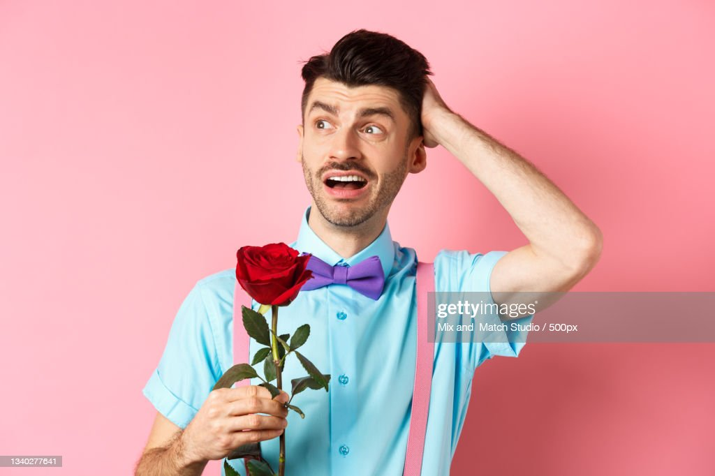 Young Man Holding Rose While Standing Against Red ...