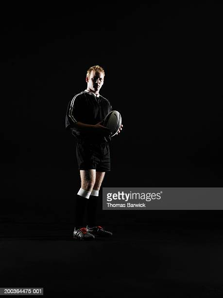 Young man holding rugby ball, portrait