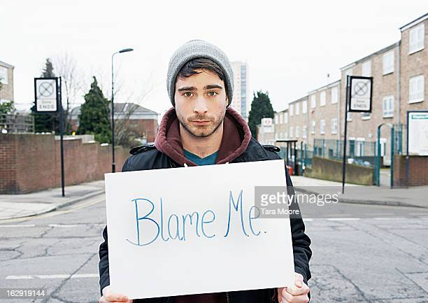 young man holding sign in urban street - blame stock pictures, royalty-free photos & images