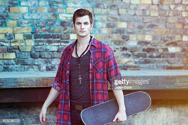 Young man holding skateboard and standing in urban environment
