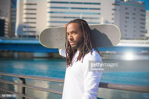 young man holding skateboard on sea side park - ドレッドロック ストックフォトと画像