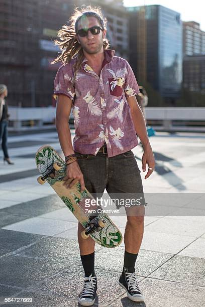 Young man holding skateboard, portrait