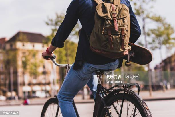 young man holding skateboard riding bicycle in the city - mid section stock photos and pictures