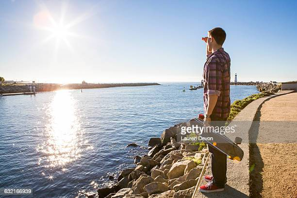 Young man, holding skateboard, standing at waters edge, looking at view
