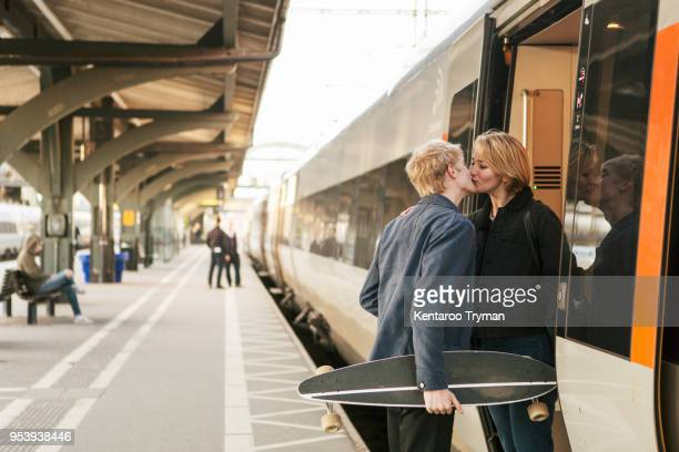 Young man holding skateboard while kissing teenage girl at doorway of train