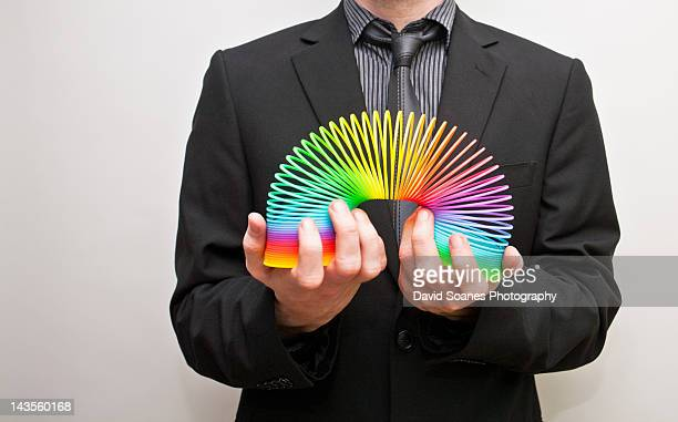 young man holding slinky - metal coil toy stock photos and pictures