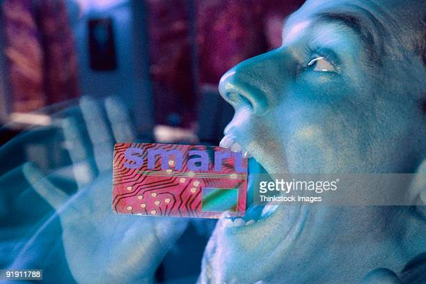 Young man holding SMART card in his mouth