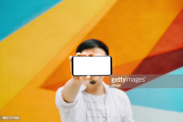 young man holding smartphone on hand with a blank screen against colourful background - multi colored background stock pictures, royalty-free photos & images
