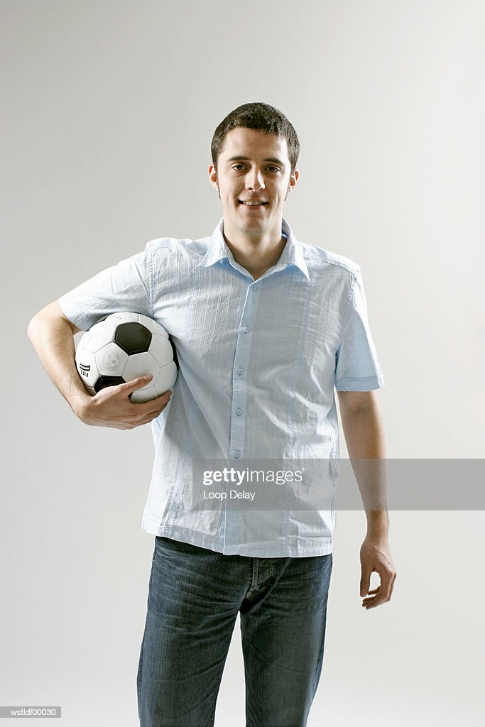 Young man holding soccer ball : ストックフォト