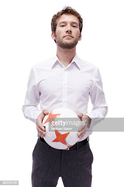 Young man holding soccer ball, portrait