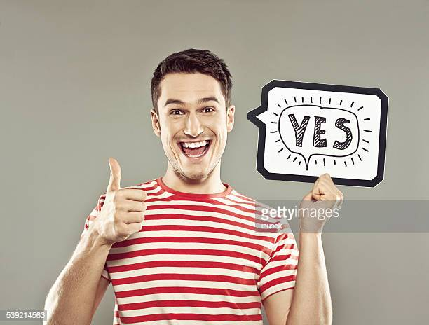 young man holding speech bubble with text yes - single word stock pictures, royalty-free photos & images