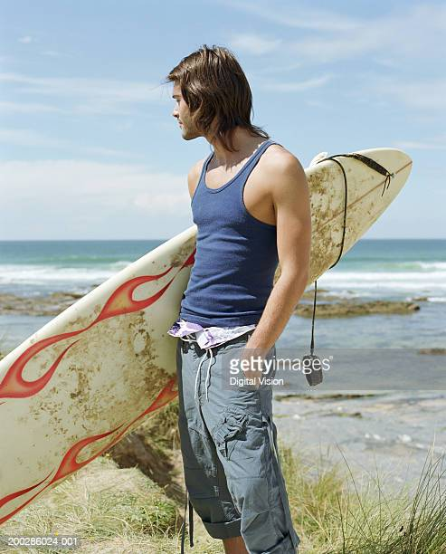 Young man holding surfboard under arm, other hand in pocket, side view