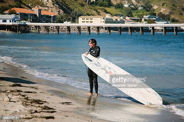 Young man holding surfboard walking out of the ocean in Malibu Los Angeles California USA