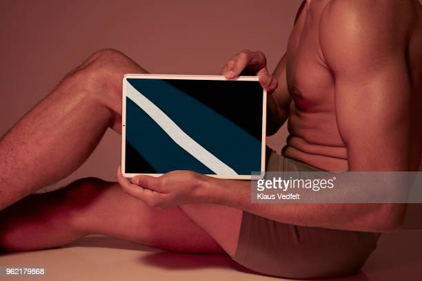Young man holding tablet in front of body to show leg bone