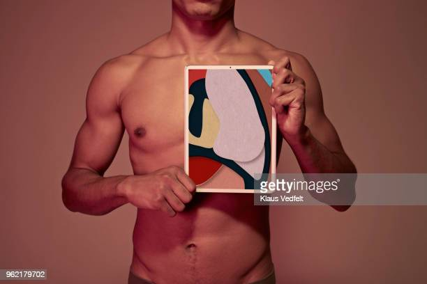 Young man holding tablet in front of chest to display lung