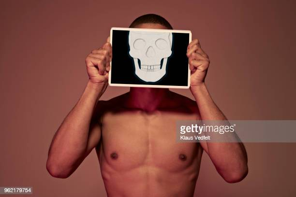Young man holding tablet in front of face to display skull