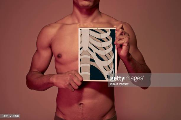 Young man holding tablet in front ofYoung man holding tablet in front of chest to display rib bones