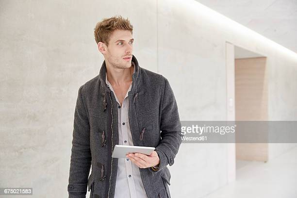 Young man holding tablet looking around in building