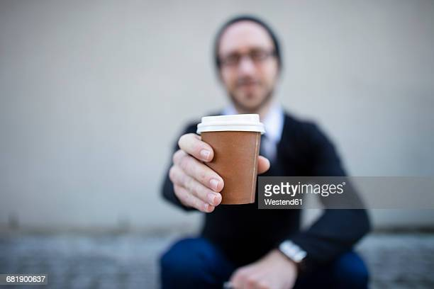 young man holding takeaway coffee - take away food stock pictures, royalty-free photos & images