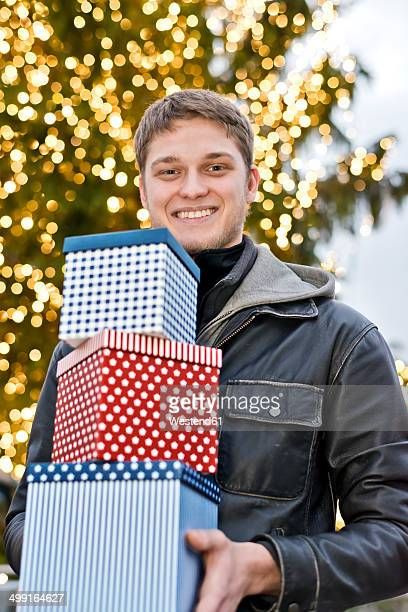 Young man holding three gift boxes in front of lighted Christmas tree