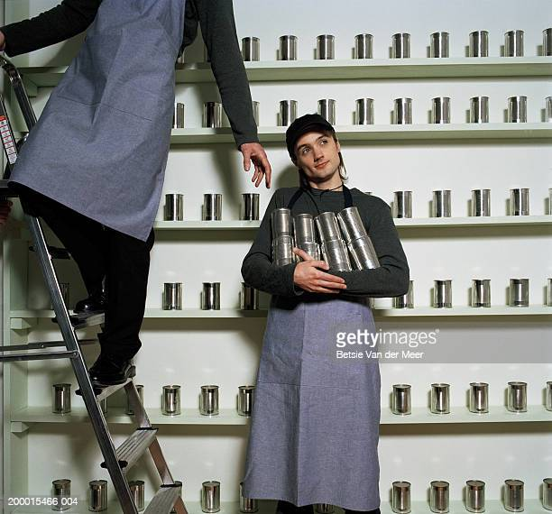 Young man holding tin cans beside man on stepladder