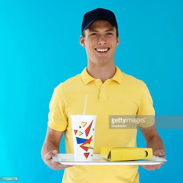 Young man holding tray with fast food, smiling, waist up