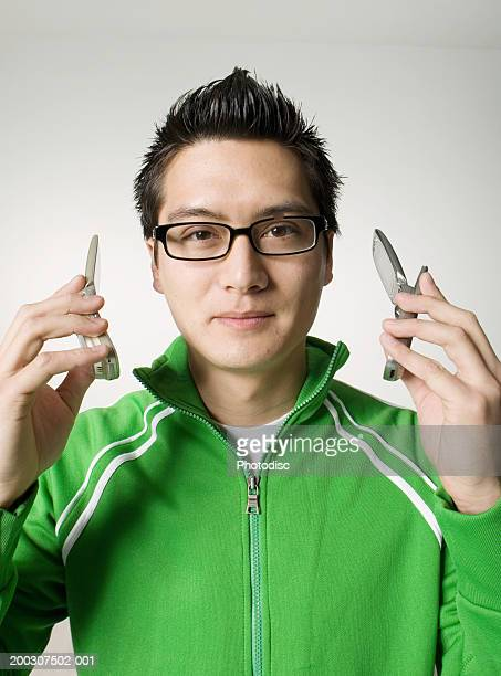 Young man holding two mobile phones, posing in studio, portrait