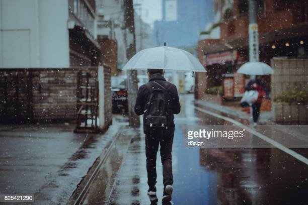 Young man holding umbrella walking in snow in city street